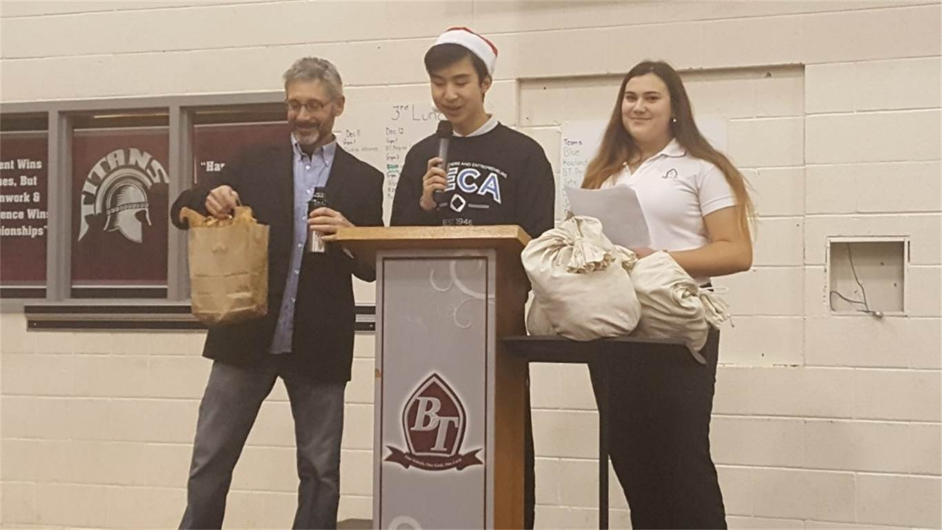 Comedian and speaker of the Funny Money presentation, Steve Levin, receiving a thank you and a gift from Daniel Mun (President of DECA) and Erica Carnicelli (President of Finance Club) at the end of the Funny Money financial literacy assembly.